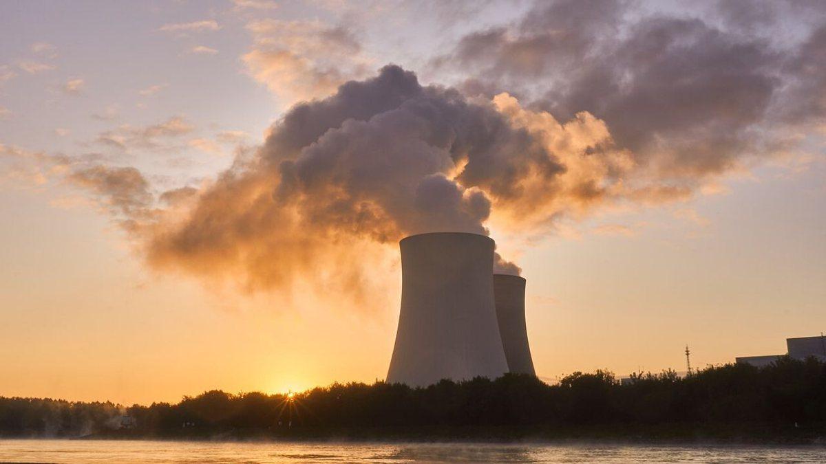 Usina nucelar emitindo gases para atmosfera durante o entardecer.
