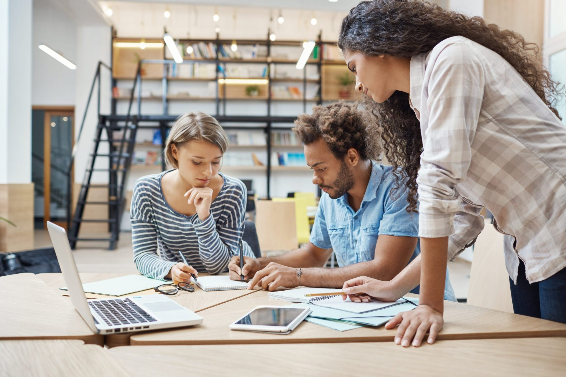 mulher e dois homens em escritório fazendo gerenciamento de projetos, com computador aberto na mesa