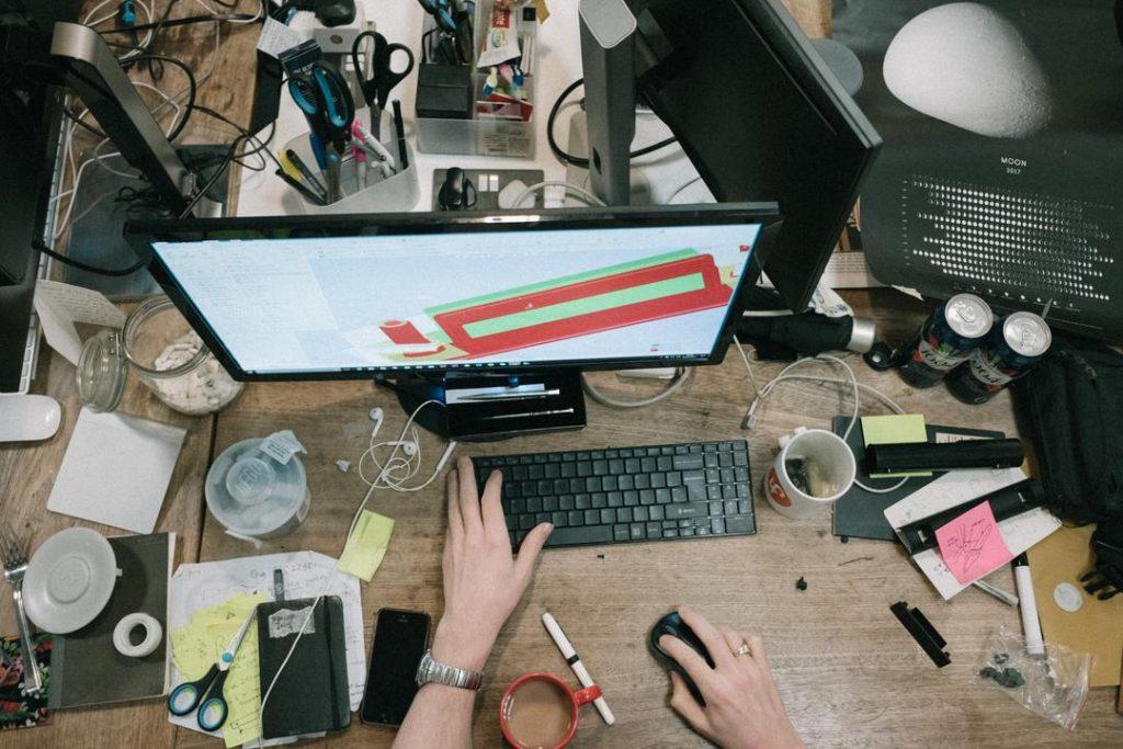 Mesa com tela de computador mouse e teclado e diversos utensílios de escritório totalmente desorganizados
