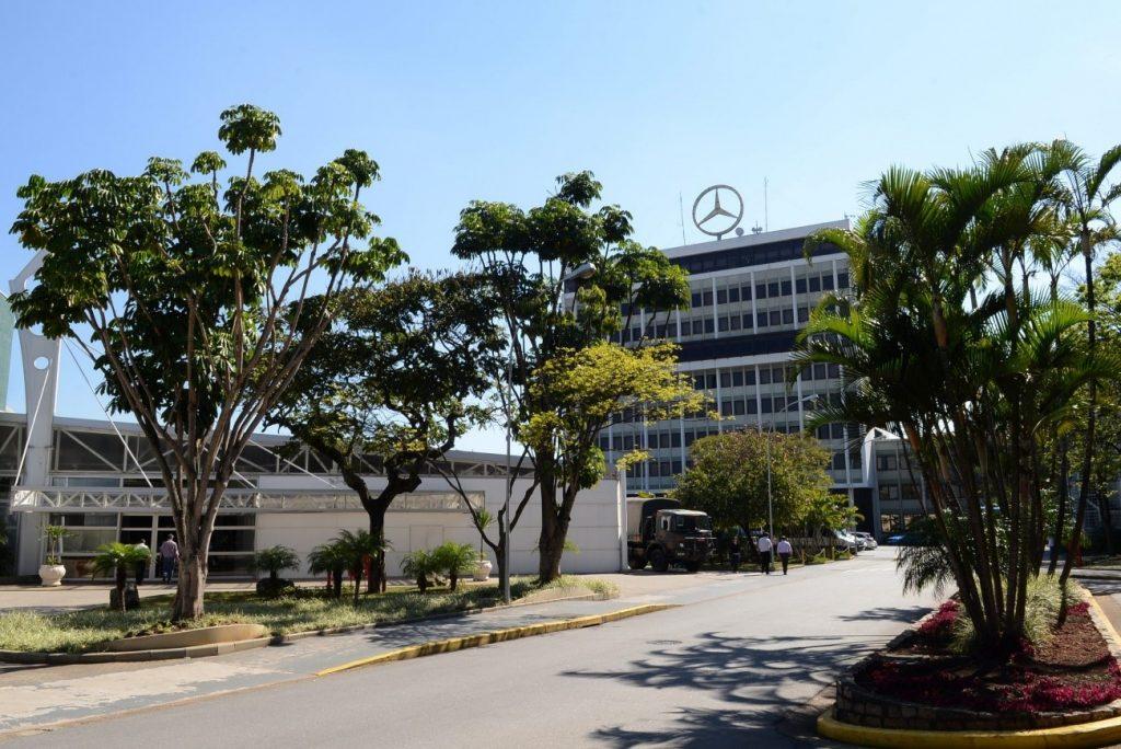 Ao fundo, o prédio administrativo da Mercedes-Benz cercado por árvores na paisagem