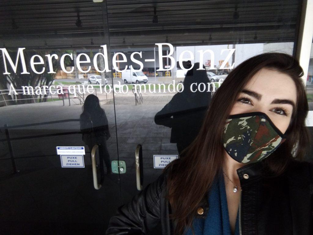 "Vidro ao fundo da imagem escrito ""Mercedes-Benz a marca que todo mundo confia"". Estou posicionada a frente do lado direito, usando máscara e jaqueta"