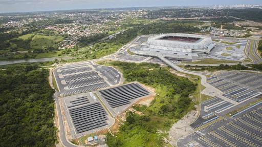 Vista aérea da arena Pernambuco. Na foto é possível ver a usina solo nas áreas ao redor do estádio, e ao fundo, é possível ver a arena e a cidade.