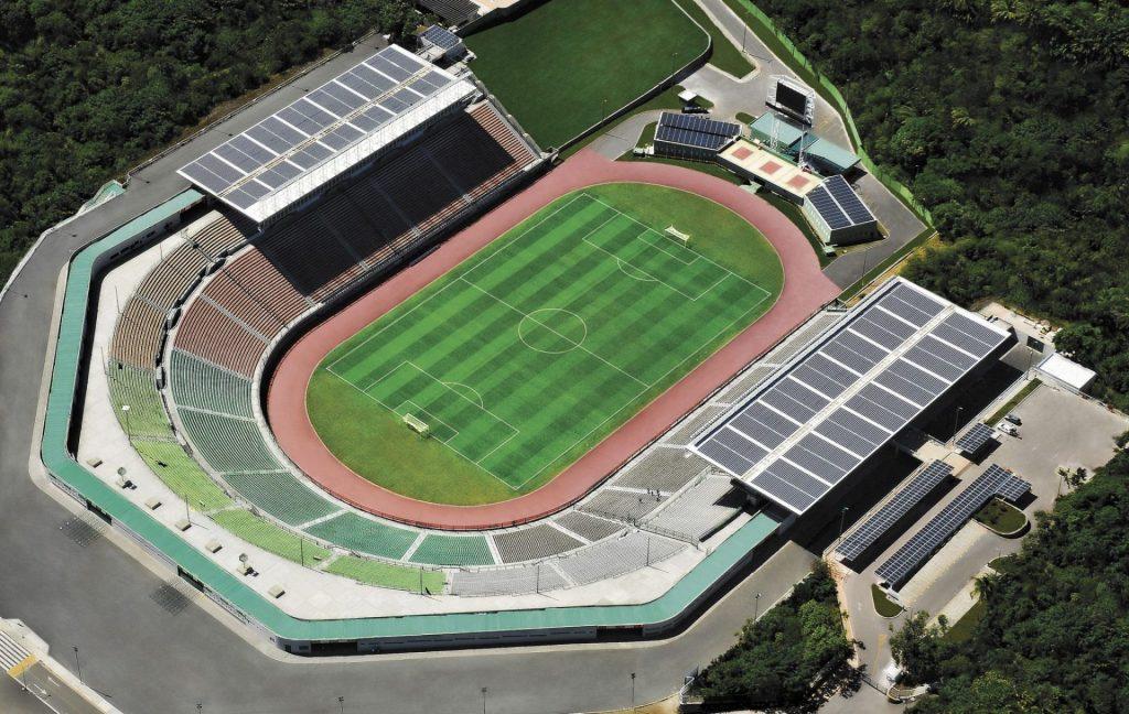 Vista de cima do estádio de Pituaçu. Na foto é possível ver as arquibancadas do estádio, seu gramado verde e a cobertura acima das arquibancadas, onde se encontra os módulos fotovoltaicos.