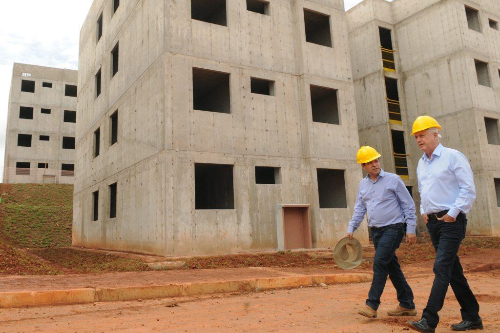 Dois engenheiros com capacete amarelo caminhando em canteiro de obra de apartamentos em parede de concreto armado.
