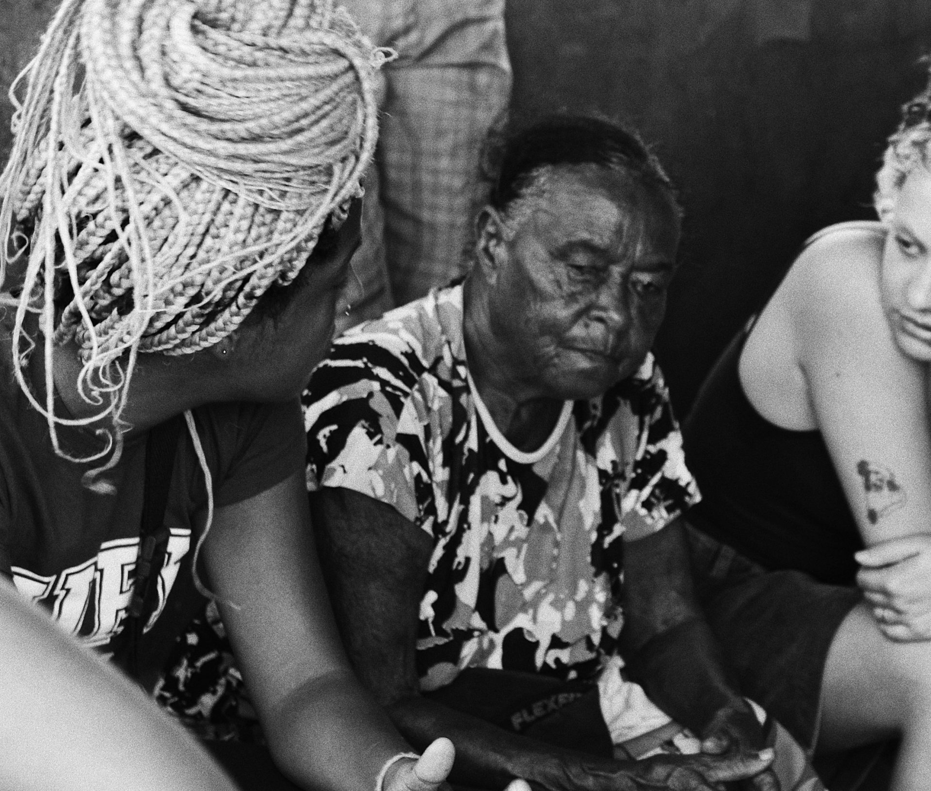 Jovens universitários conversando com senhora da comunidade, imagem em preto e branco