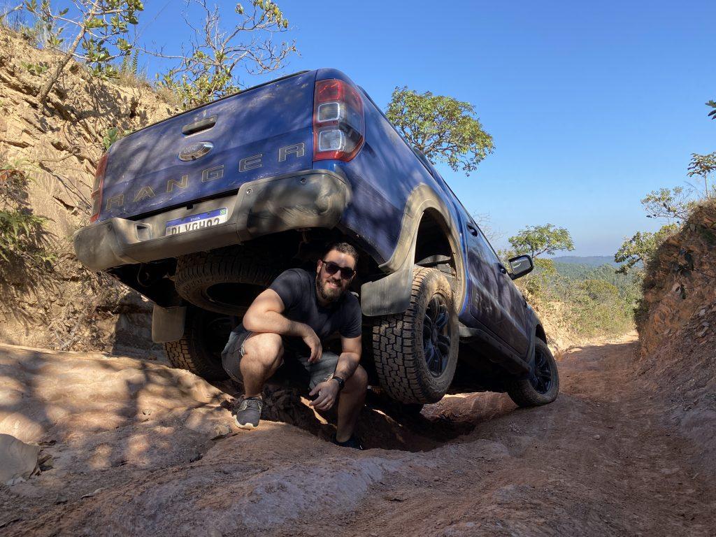 Homem fazendo pose para foto sob roda de veículo em estrada de terra