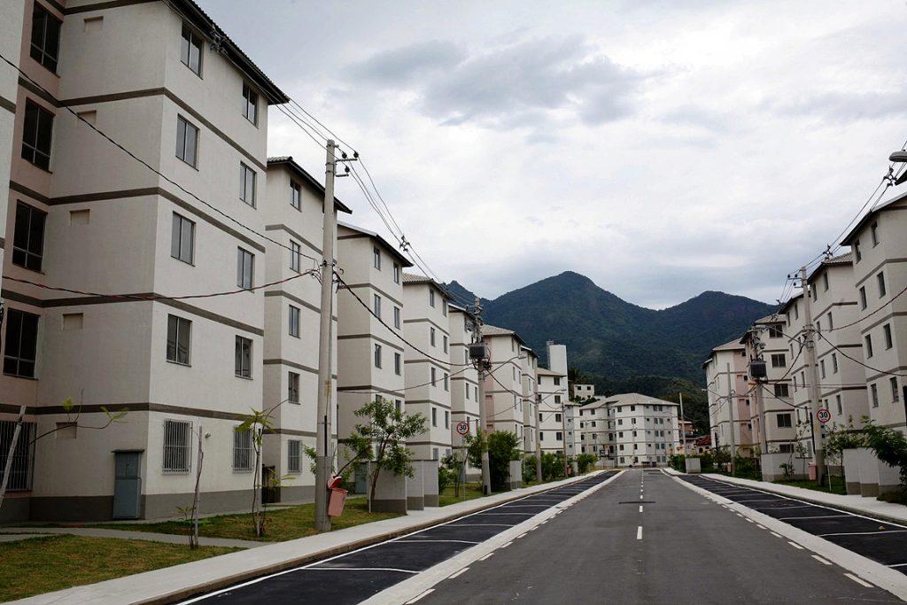 Vista de conjunto habitacional de apartamentos, com rua pavimentada entre blocos de edificações com 5 pavimentos.