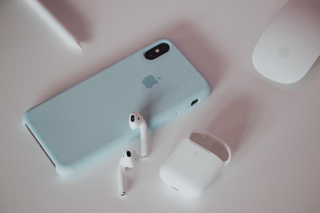 Iphone e fones wireless sobre mesa branca