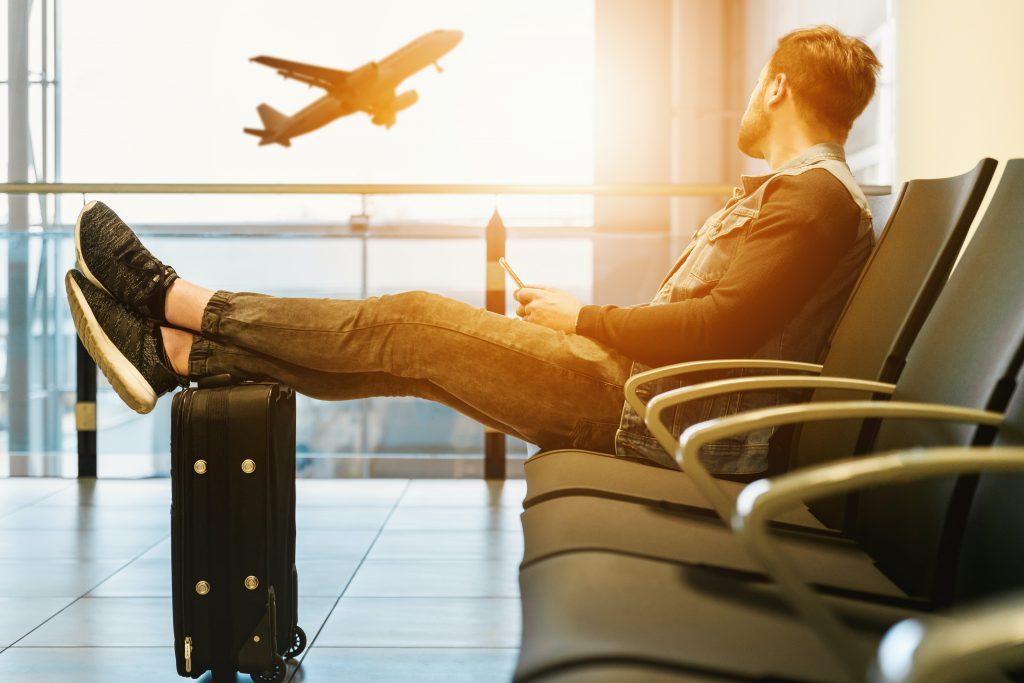 Homem sentado em aeroporto com pés em cima da mala, olhando avião levantar voo