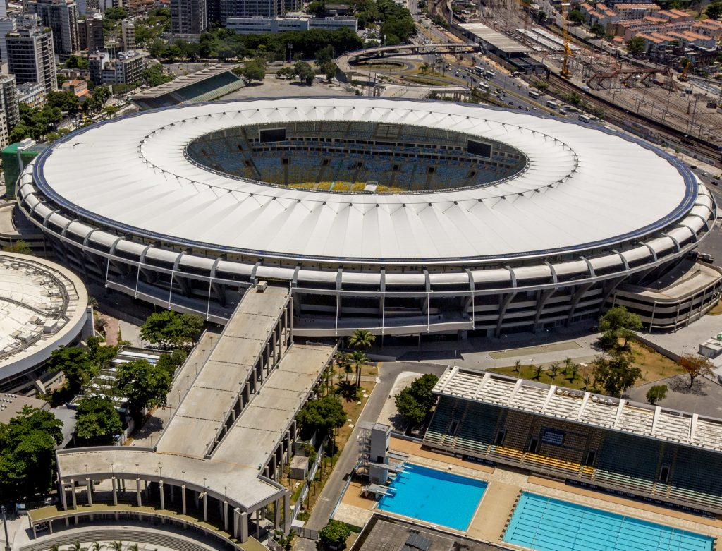 Vista superior do estádio Maracanã. Na imagem é possível visualizar os módulos fotovoltaicos no anel externo da cobertura do estádio. Além disso, também é possível ver um pouco das arquibancadas e a cidade ao redor do estádio.