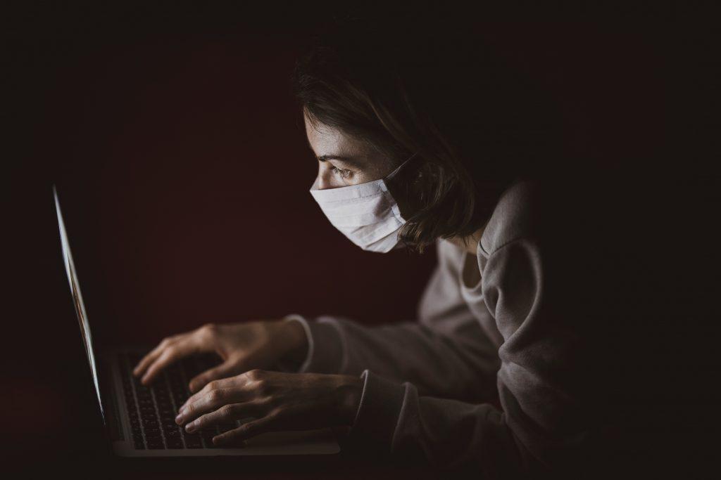 mulher de máscara usando computador, imagem com fundo preto