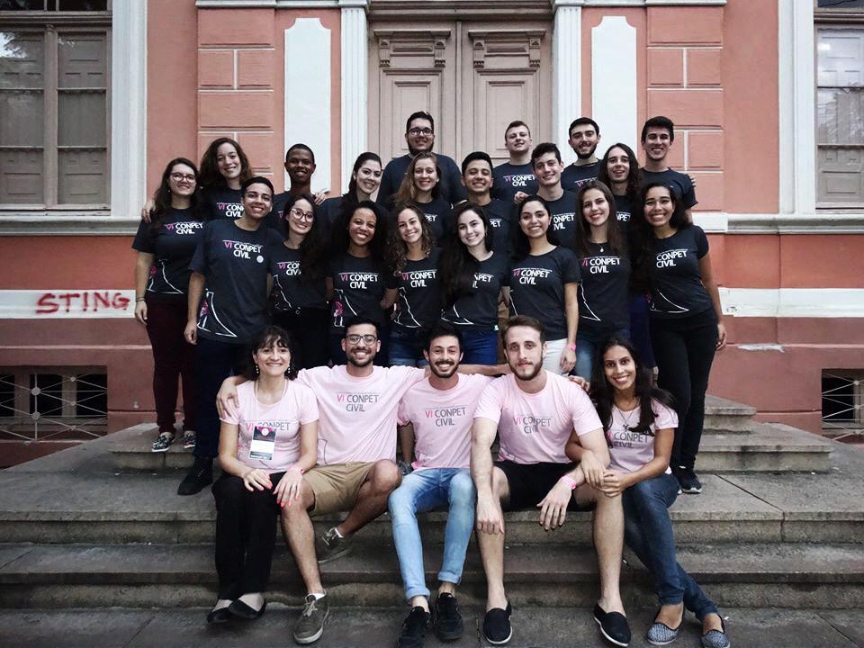 grupo de alunos de extensão universitária em frente a uma escadaria sorrindo para a foto