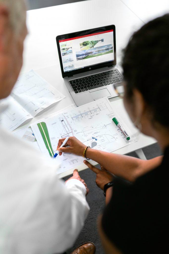 homem e mulher analisando planta baixa, representando engenharia civil x arquitetura