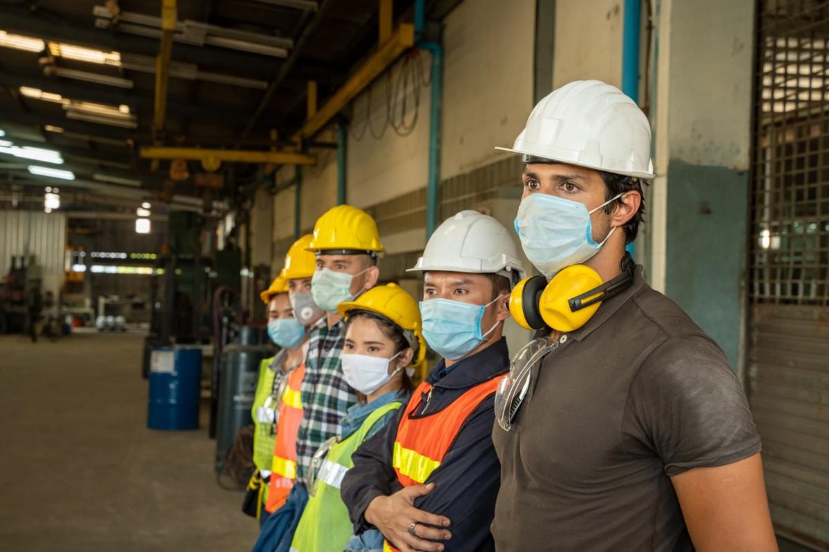 Engenheiros e técnicos da equipe usando máscara protetora para impedir a propagação da Covid-19 e a infecção pela doença.