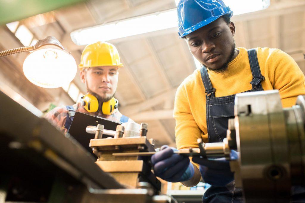Engenheiro de fábrica afro-americano sério e concentrado no capacete de segurança ajustando a fresadora e juntando os detalhes, enquanto o inspetor qualificado examina seu trabalho e controla o processo de produção.