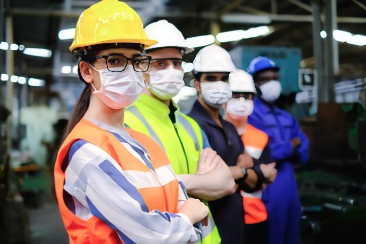 Funcionários de fábrica usando máscara para trabalhar durante pandemia do novo coronavírus