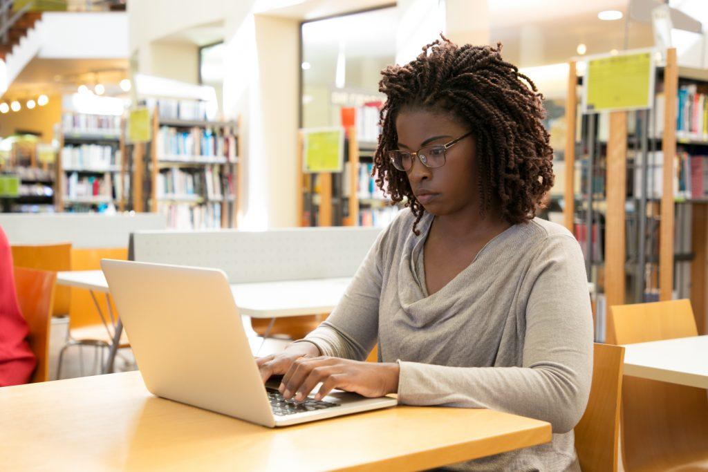 Jovem negra de óculos estudando na biblioteca usando um notebook branco, representando aluna estudando para conseguir estágio