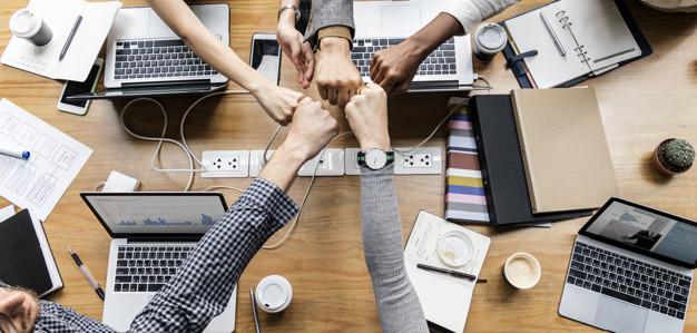 mãos juntas em cima de uma estação de trabalho