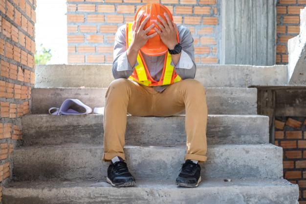 Engenheiro na obra sentado em escada estressado