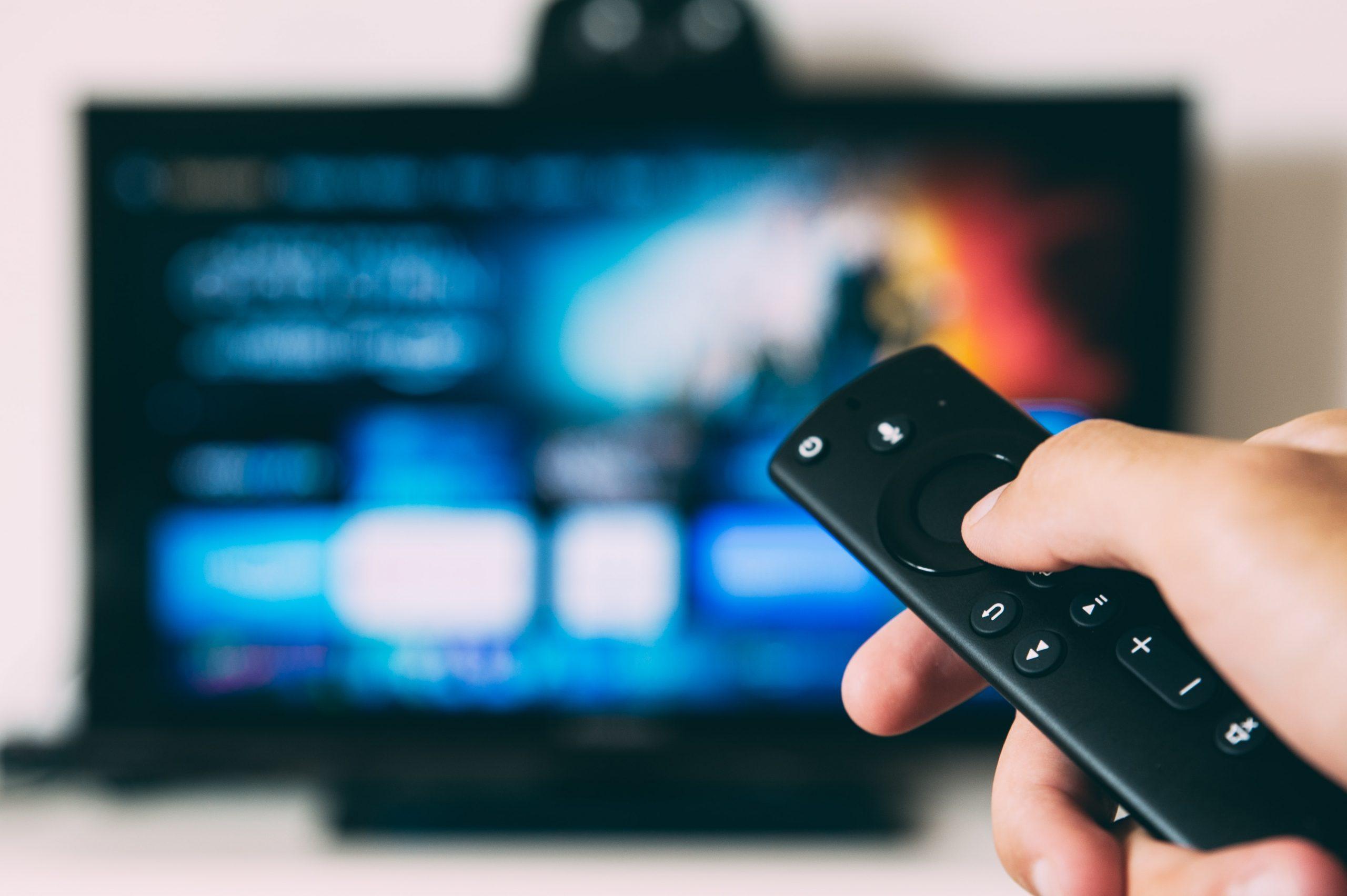 imagem de mão apertando controle remoto e televisão ao fundo com Amazon Prime Video