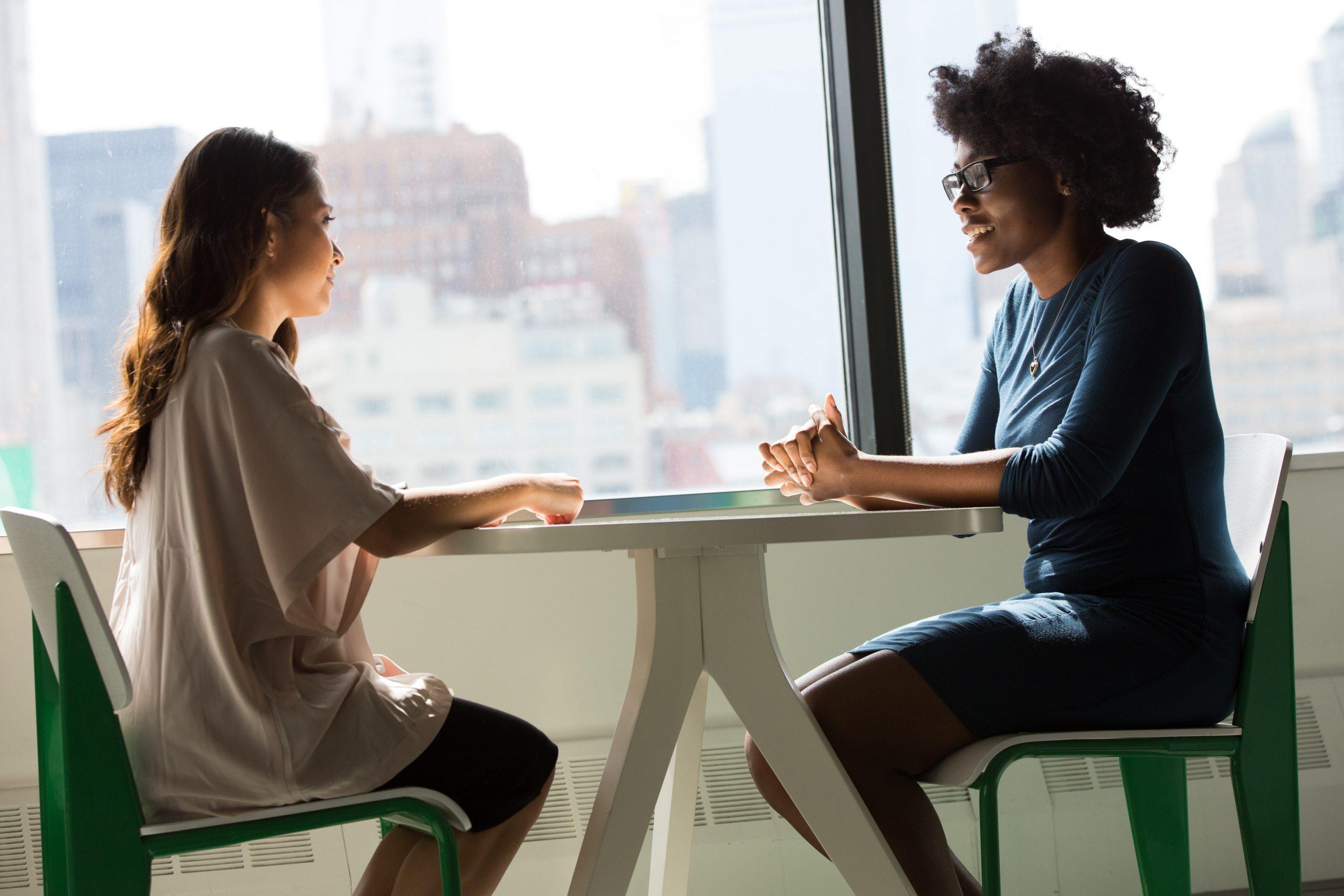 duas mulheres sentadas se frente para outra