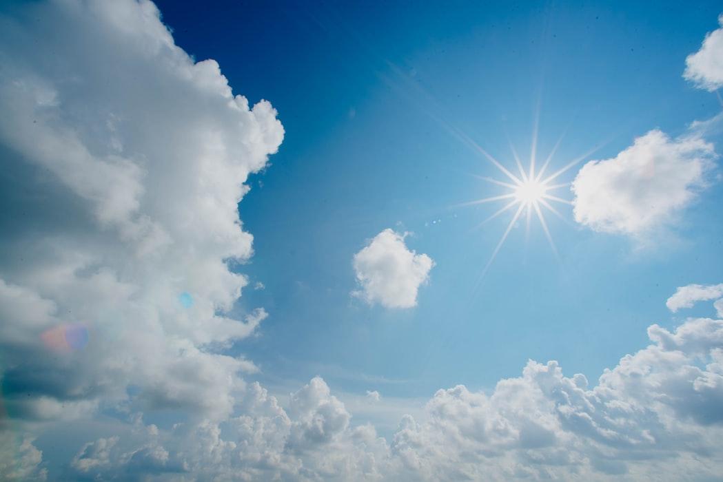céu azul com nuvens brancas e sol brilhando