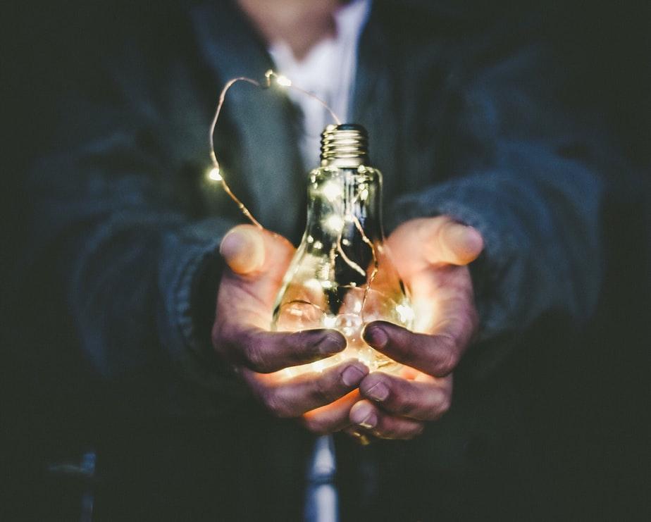 homem segurando lâmpada em mãos representando a sustetabilidade