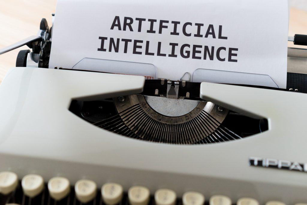 imagem ilustrativa de inteligência artificial, com nome escrito em inglês em papel colado em máquina de escrever
