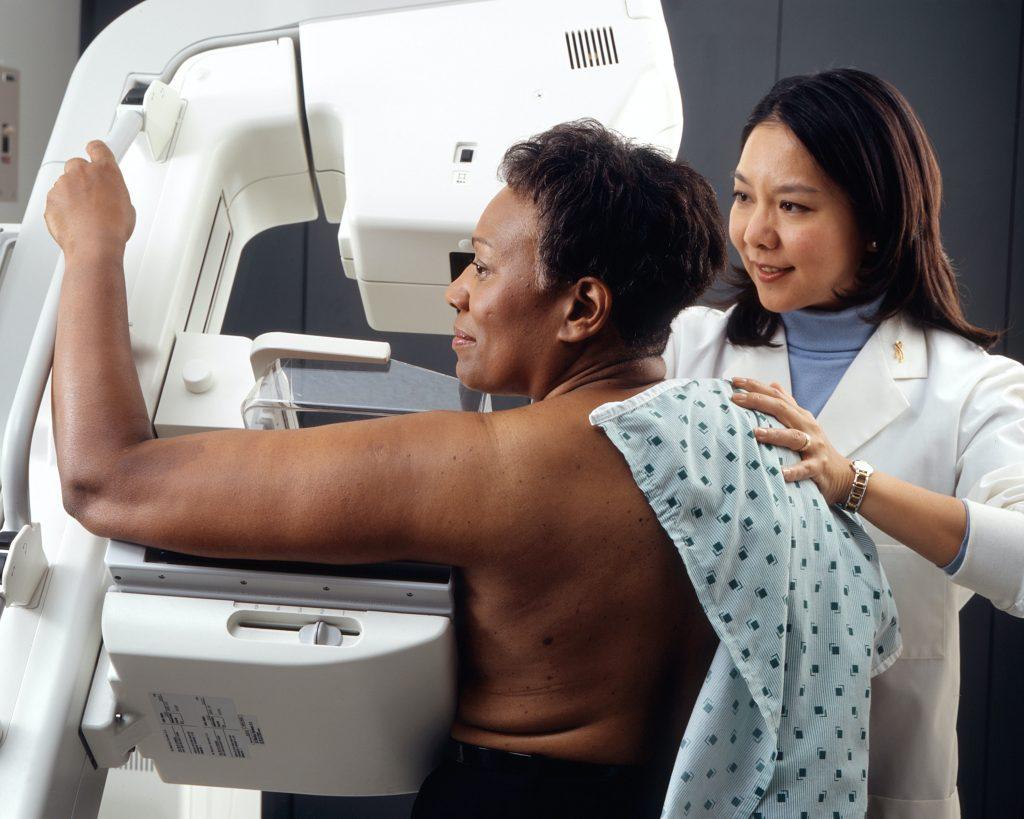 mulher negra realizando mamografia com técnica asiática orientando