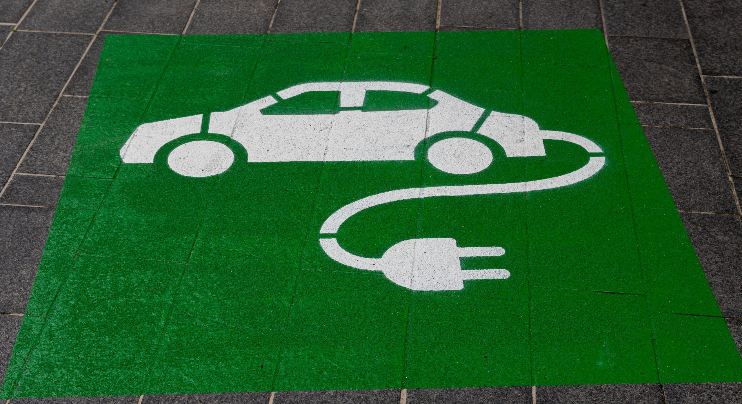imagem de parada de veículos elétricos para abastecimento. Carro elétrico pintado de branco em retângulo verde no chão