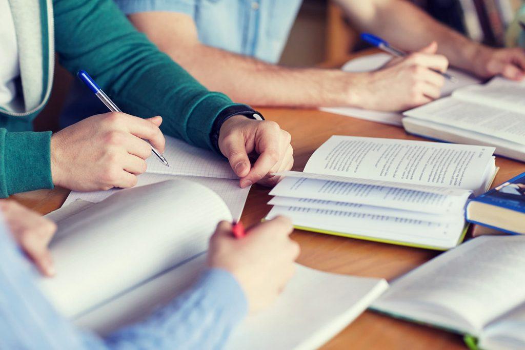Pessoas estudando com livros e cadernos em cima da mesa.