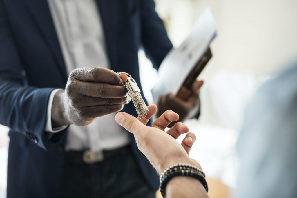 imagem ilustrativa de homem entregando chaves de casa em nas mãos de outra pessoa, representando mudança de lar
