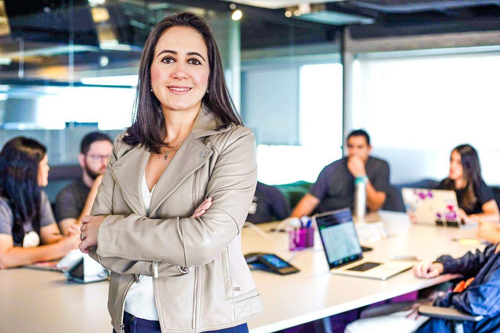cristina junqueira, formada em engenharia e CEO da Nubank a frente da imagem, com outros funcionários ao fundo