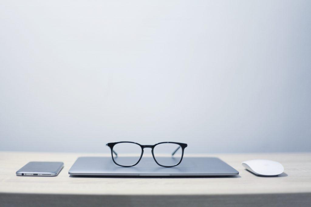 imagem de notebook com óculos em cima dele e celular ao lado, representando marketing e tecnologia