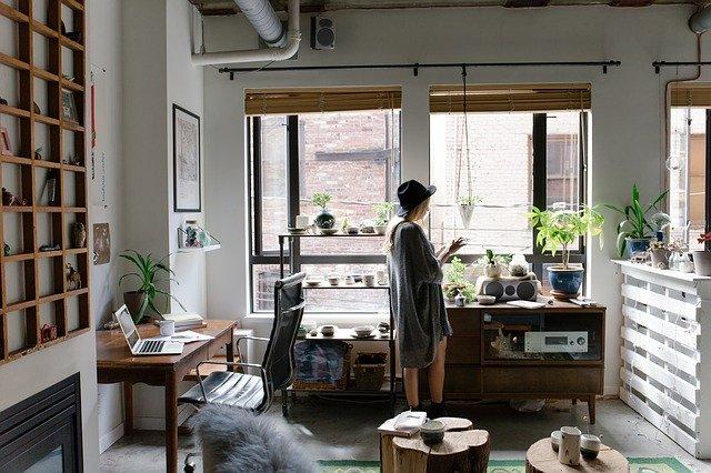 Cantinho da casa preparado para home office. Mulher em pé próximo a sua escrivaninha.