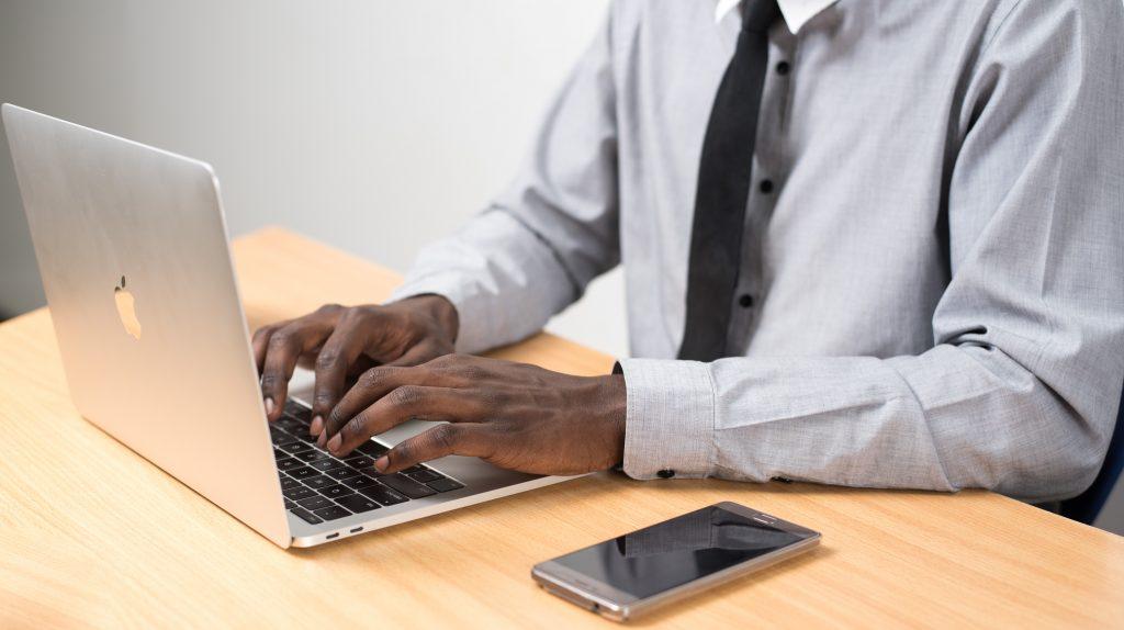 homem negro de terno usando computador em casa para home office