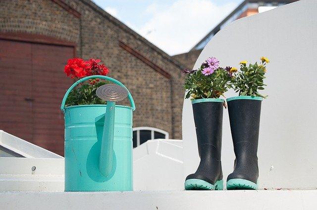 Ornamentos - regador ao lado de galocha, ambos servindo de vaso de plantas