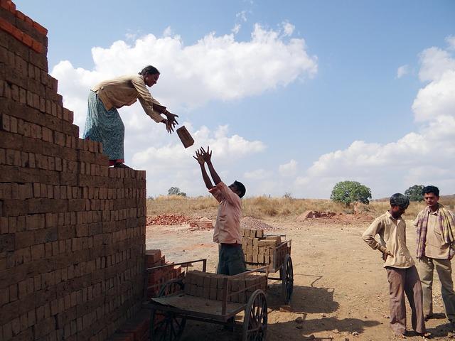 mulher em cima de pilha de tijolo, lançando um deles para um homem