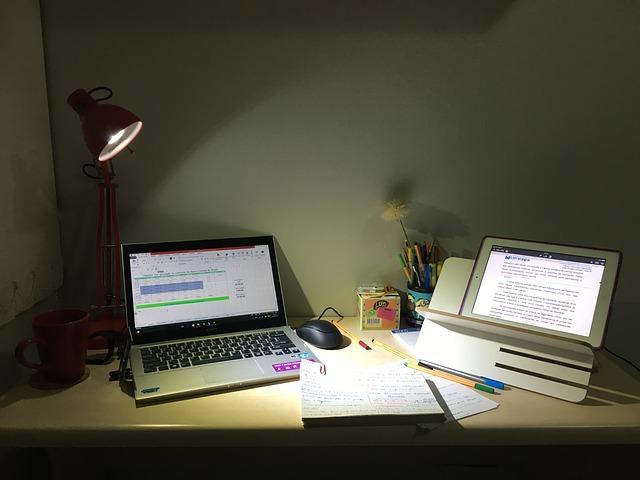 Escrivaninha com notebook e tablet ilustrando o ensino à distância
