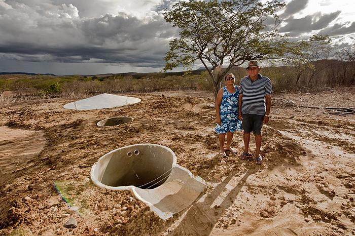 Cisterna para produção em terreno, com homem e mulher