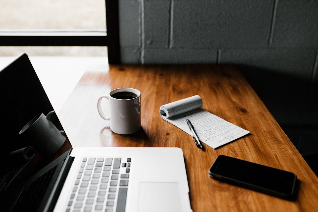 Tampo de mesa marrom sobre o qual estão um macbook pro, uma caneca branca com café, um bloco de notas e uma caneta e um celular que podem ser usados para leitura de diversos títulos.