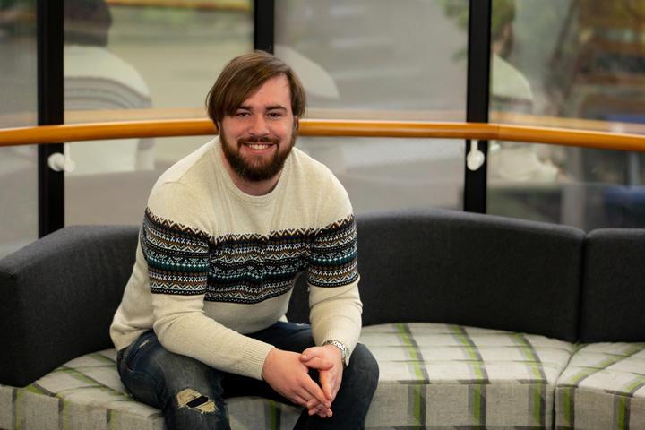 Chris Boniface sentado em sofá e sorrindo para a câmera