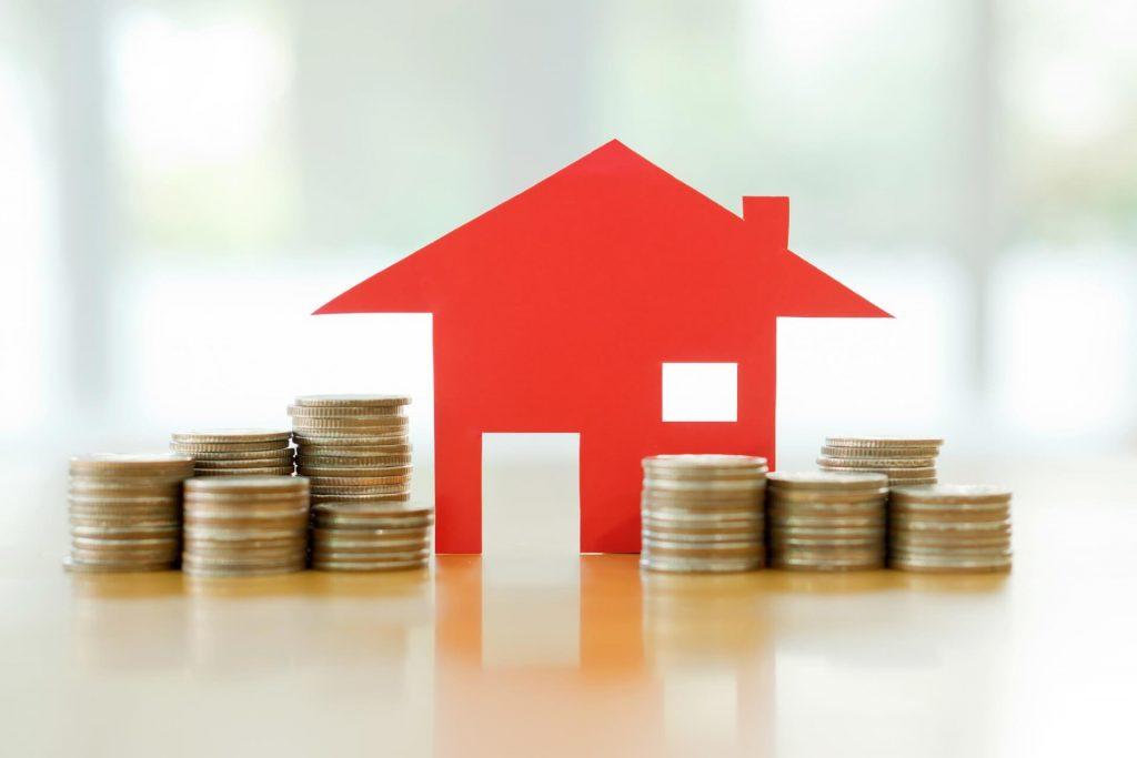 Representação de casa em papel sobre uma mesa com pilhas de moedas ao redor