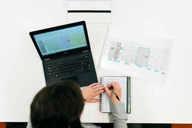 pessoa estudando sobre mesa usando notebook e caderno, fazendo anotações e ilustrando arquitetos e engenheiros