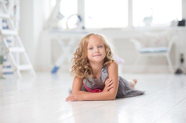 imagem de criança loira deitada em chão