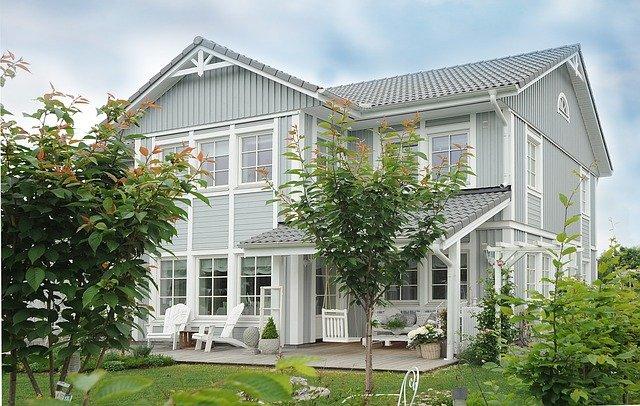casa cinza azulado com detalhes brancos e jardim com grama verde representando arquitetura saudável