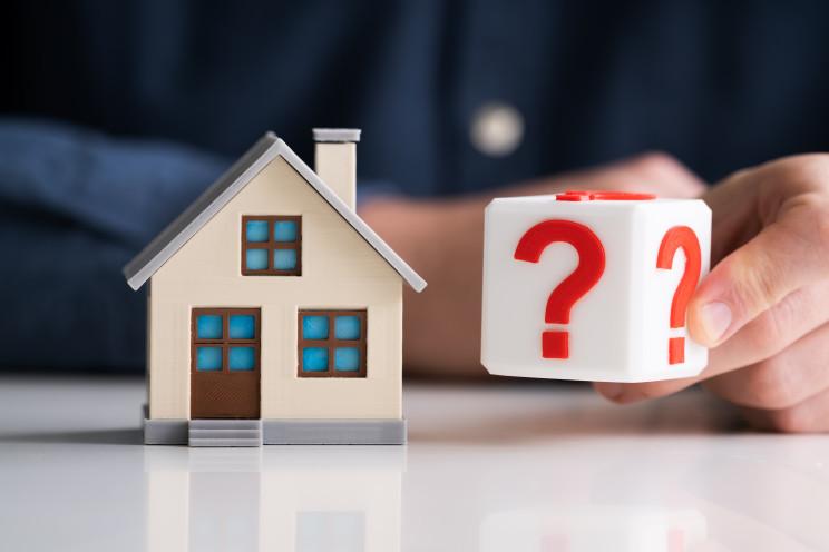 Desenho de casa ao lado de dado com pontos de interrogação nas faces, indicando incerteza. Ilustra a alta dos preços dos materiais de construção civil.