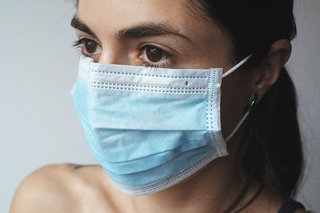 mulher usando máscara representando Covid 19
