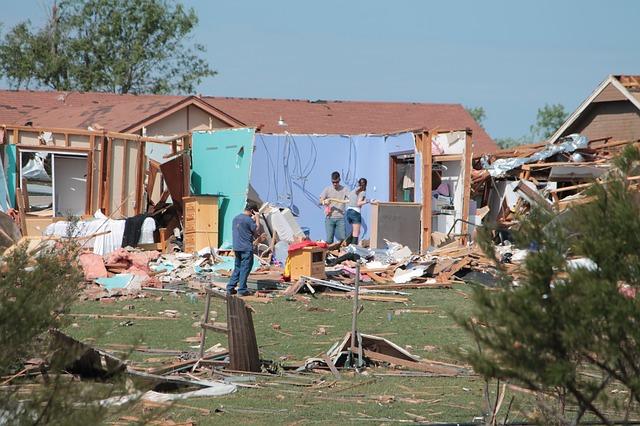 população mexendo em casas destruídas por ciclones