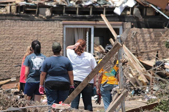 Famílias olhando para destruição causada por ciclone